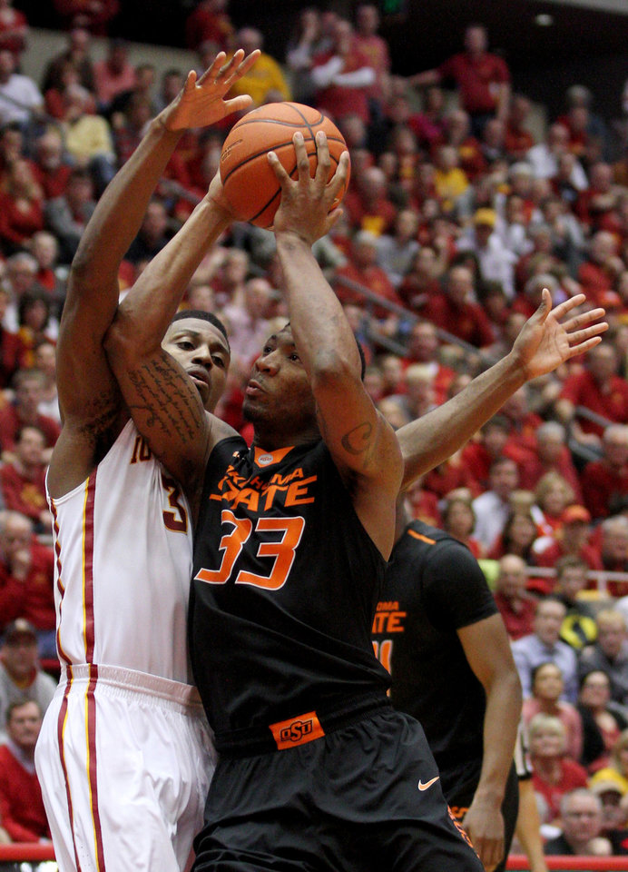Photo - Oklahoma State guard Marcus Smart draws a foul on Iowa State forward Melvin Ejim as he drives to the basket during the second half of an NCAA college basketball game in Ames, Iowa, Saturday, March 8, 2014. Iowa State won 85-81 in overtime. (AP Photo/Justin Hayworth)