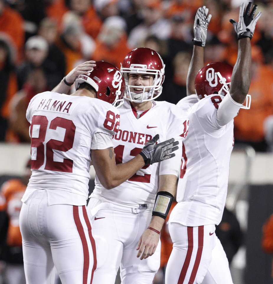 Photo - Oklahoma's Landry Jones (12) and Oklahoma's James Hanna (82) celebrate after the Bedlam college football game between the University of Oklahoma Sooners (OU) and the Oklahoma State University Cowboys (OSU) at Boone Pickens Stadium in Stillwater, Okla., Saturday, Nov. 27, 2010. Photo by Bryan Terry, The Oklahoman