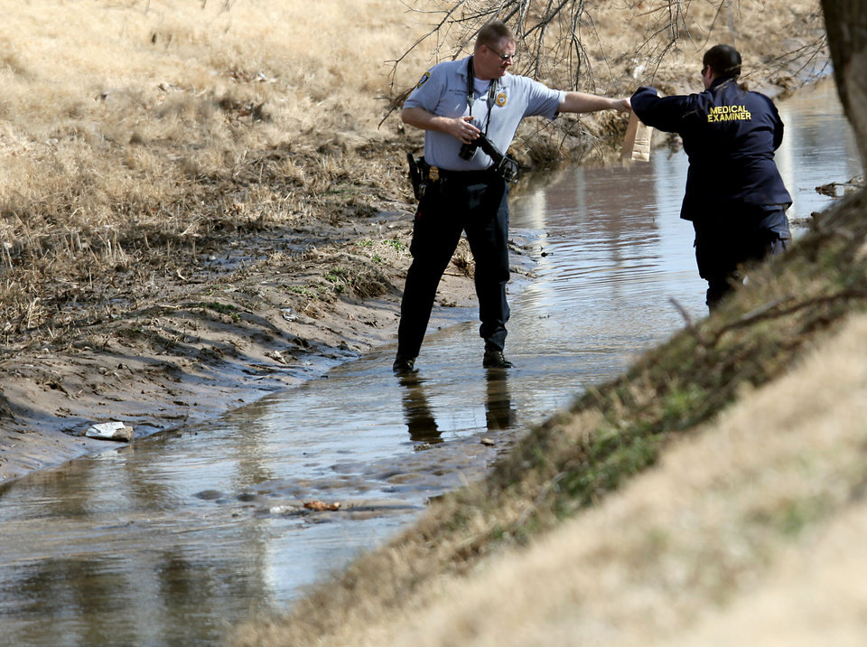 Photo - Officials investigate a scene where a body was found near General Pershing and Villa  in Oklahoma City on Tuesday, Feb. 10, 2009. By John Clanton, The Oklahoman