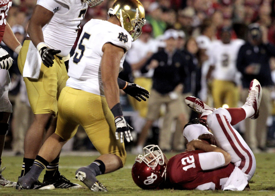 Photo - Oklahoma quarterback Landry Jones (12) lies on the ground after being sacked during the first half of the college football game between the University of Oklahoma Sooners (OU) and the Fighting Irish of Notre Dame (ND) at Gaylord Family-Oklahoma Memorial Stadium in Norman, Okla., on Saturday, Oct. 27, 2012. Photo by Steve Sisney, The Oklahoman