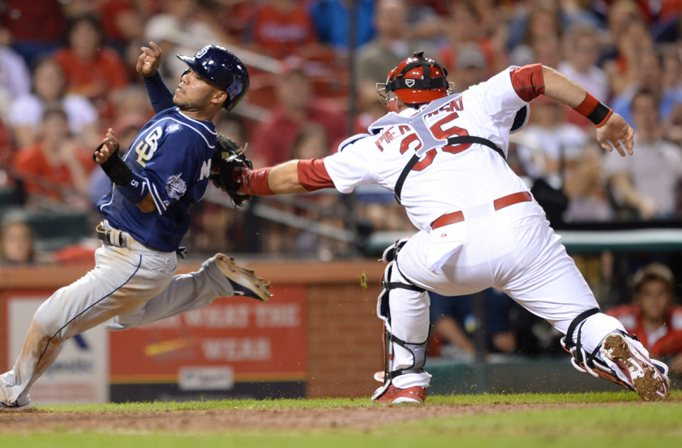 Photo - St. Louis Cardinals' A.J. Pierzynski (35) tags out San Diego Padres' Alexi Amarista at the plate in the ninth inning in a baseball game, Thursday, August 14, 2014, at Busch Stadium in St. Louis. (AP Photo/Bill Boyce)