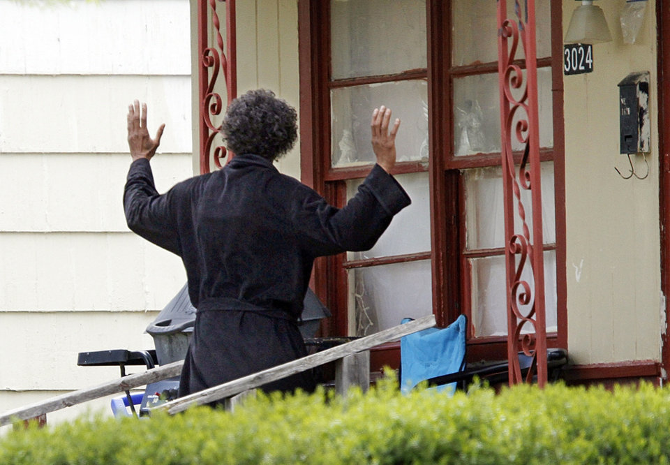 A suspect from the MidFirst Bank robbery in Oklahoma City, holds his hands up as police and FBI surrounded a house at 3024 NE 16th street, Friday April 12, 2013. Photo By Steve Gooch, The Oklahoman