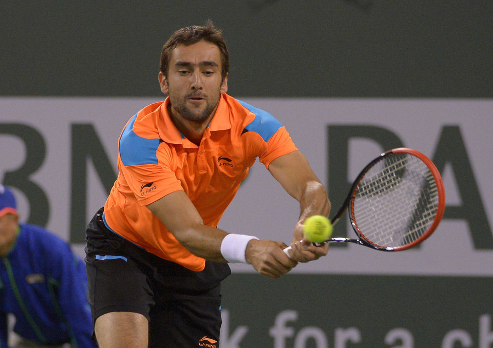 Photo - Marin Cilic, of Croatia, returns a shot to Novak Djokovic, of Serbia, during their match at the BNP Paribas Open tennis tournament, Wednesday, March 12, 2014, in Indian Wells, Calif. (AP Photo/Mark J. Terrill)