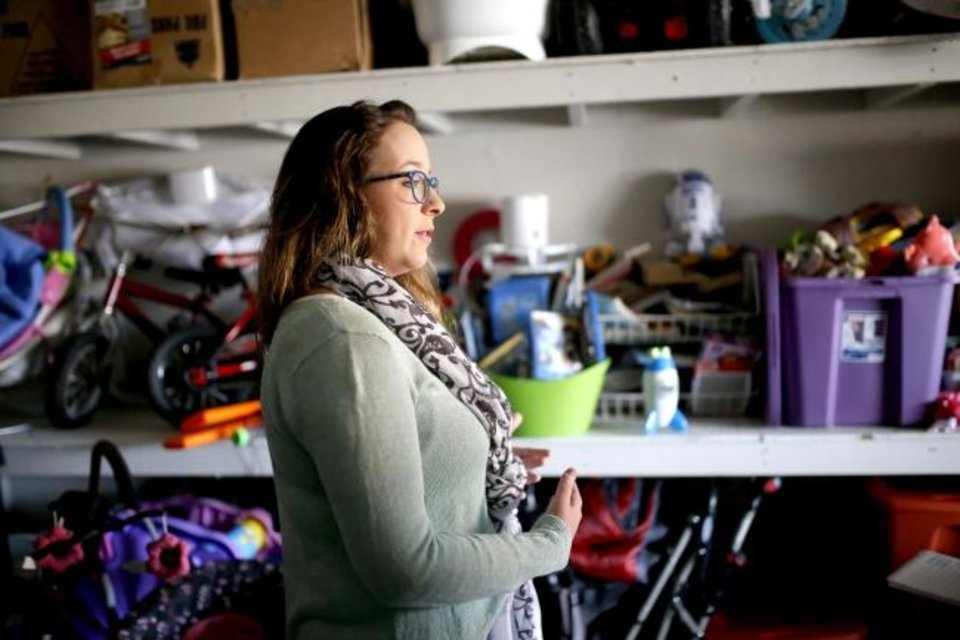 Photo -  Lynda Steele, founder of Furnishing Fatherhood, stands in her garage where she keeps many items donated for dads. [Sarah Phipps/The Oklahoman]