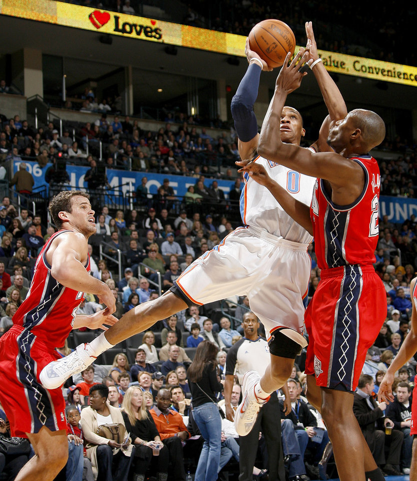 Oklahoma Cit's Russell Westbrook shoots the ball from between New Jersey's Kris Humphries, left, and Travis Outlaw during the NBA basketball game between the Oklahoma City Thunder and the New Jersey Nets at the Oklahoma City Arena, Wednesday, Dec. 29, 2010.  Photo by Bryan Terry, The Oklahoman