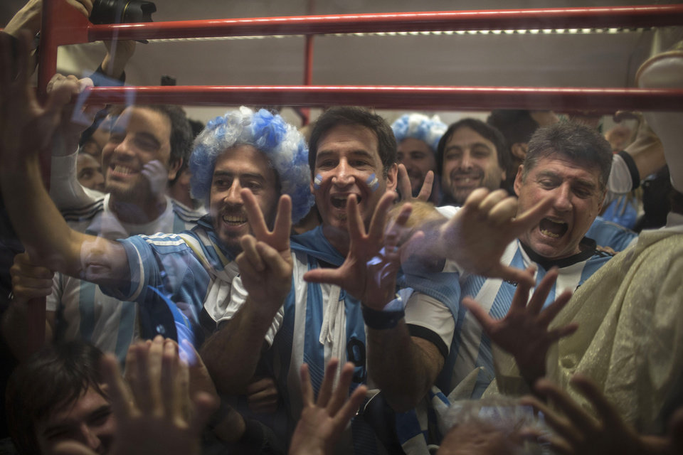 Photo - Argentina national soccer fans joke with Brazilians about their 7-1 defeat to Germany, as they ride the subway to the Itaquerao Stadium, to watch the World Cup semifinal match between the Netherlands and Argentina, in Sao Paulo Brazil, Wednesday, July 9, 2014. (AP Photo/Felipe Dana)