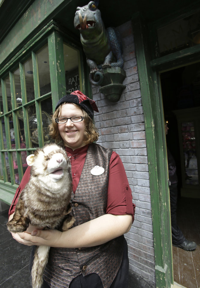 Photo - Allie Dillard shows off a ferret puppet that can be purchased at the Magical Menagerie store during a preview of Diagon Alley at the Wizarding World of Harry Potter at Universal Orlando, Thursday, June 19, 2014, in Orlando, Fla. (AP Photo/John Raoux)