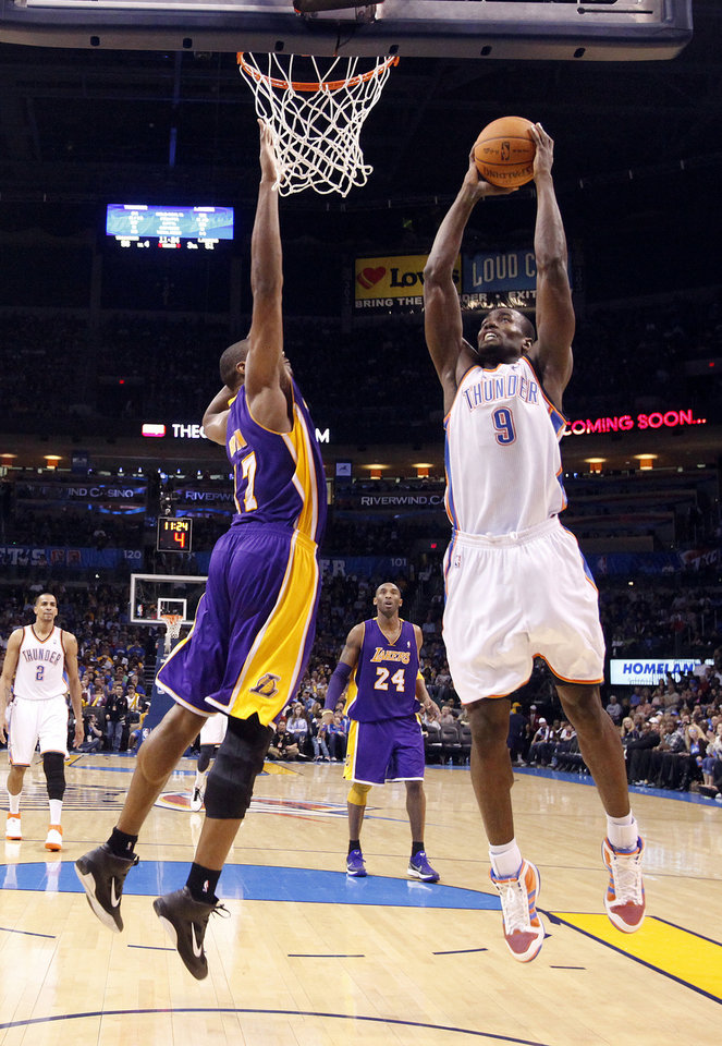 Photo - Oklahoma City's Serge Ibaka (9) dunks as Lakers' Andrew Bynum (17) defends during the NBA basketball game between the Oklahoma City Thunder and the Los Angeles Lakers, Sunday, Feb. 27, 2011, at the Oklahoma City Arena.Photo by Sarah Phipps, The Oklahoman