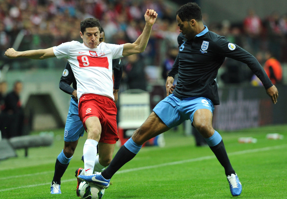 Photo -   Poland's Robert Lewandowski, left, challenges for the ball with England's Gary Cahill during their World Cup 2014 Group H qualifying soccer match at the National Stadium in Warsaw, Poland, Wednesday, Oct. 17, 2012. (AP Photo/Alik Keplicz)