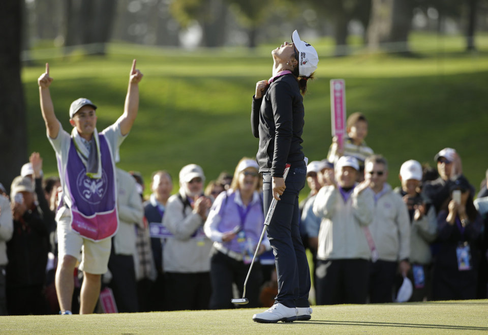 Photo - Lydia Ko of New Zealand reacts on the 18th green of the Lake Merced Golf Club after winning the Swinging Skirts LPGA Classic golf tournament on Sunday, April 27, 2014, in Daly City, Calif. Ko won the event after shooting a 3-under-par 69 to finish at 12-under-par. At left is her caddie Domingo Jojola. (AP Photo/Eric Risberg)