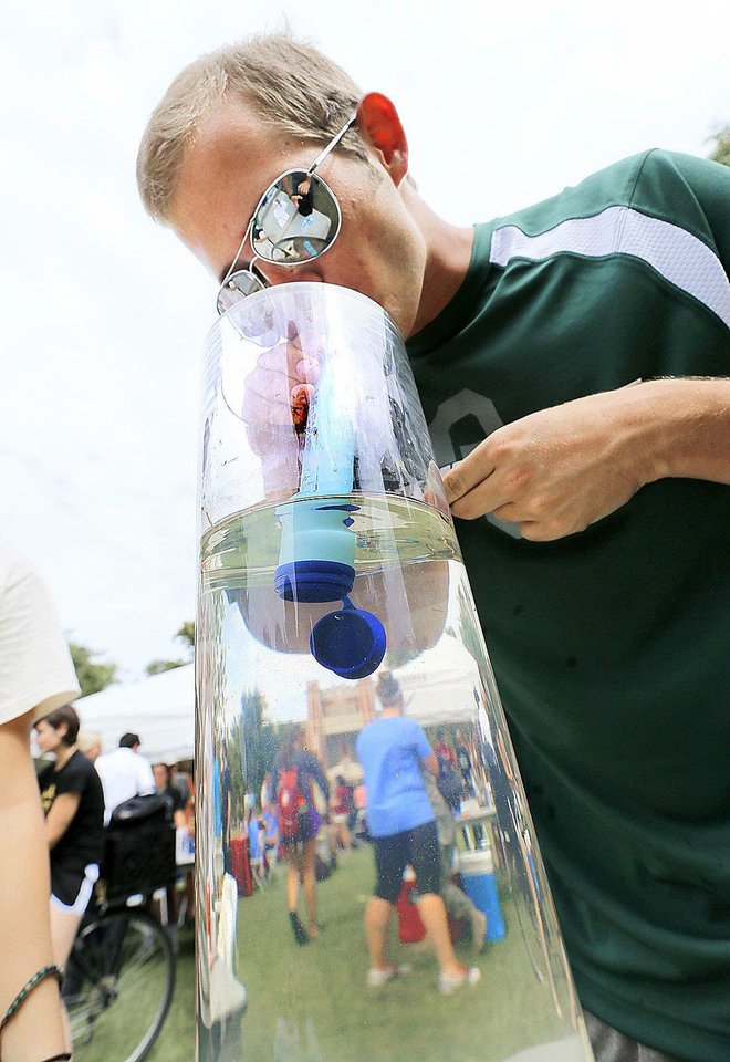 Photo - University of Oklahoma strudent Brad Moery takes a drink of duck pond water as the Water Center demonstrates a filtration device capable of producing drinkable water from pond water on Thursday, Sept. 19, 2013 in Norman, Okla.  Photo by Steve Sisney, The Oklahoman