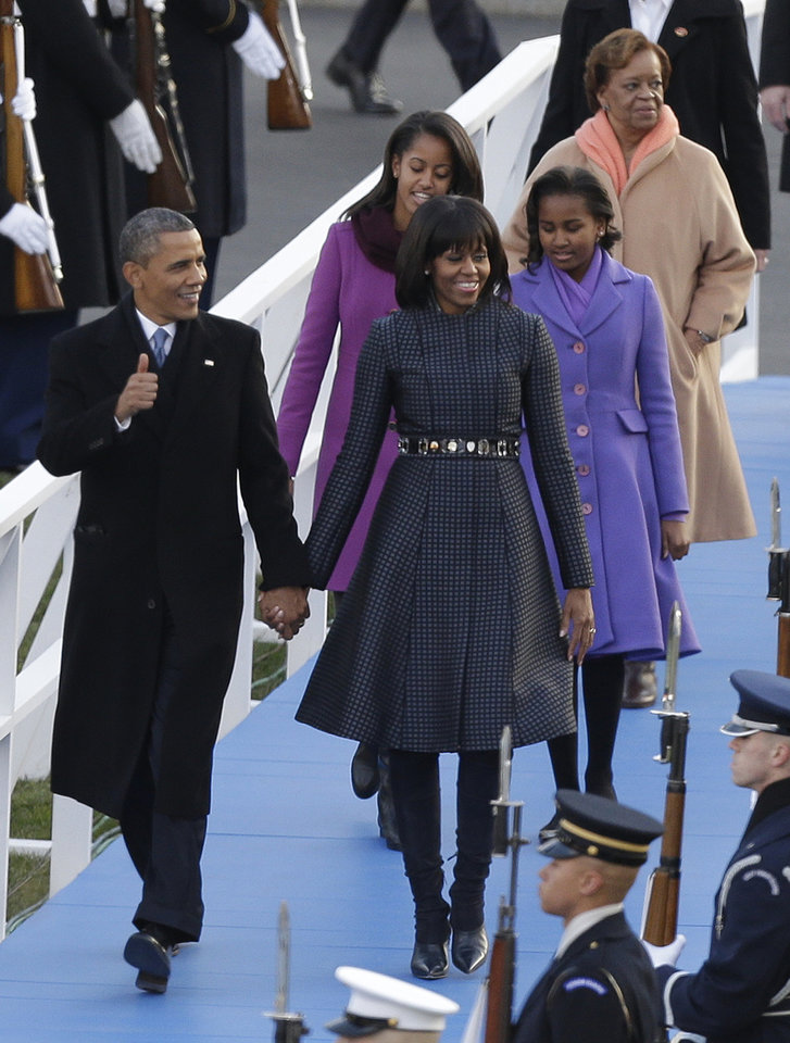 Photo - President Barack Obama, first lady Michelle Obama and Malia and Sasha Obama and Michelle Obama's mother Marian Robinson walk down to the Presidential reviewing stand in front of the White House, Monday, Jan. 21, 2013, in Washington. Thousands  marched during the 57th Presidential Inauguration parade after the ceremonial swearing-in of President Barack Obama. (AP Photo/Charlie Neibergall ) ORG XMIT: DCMS1