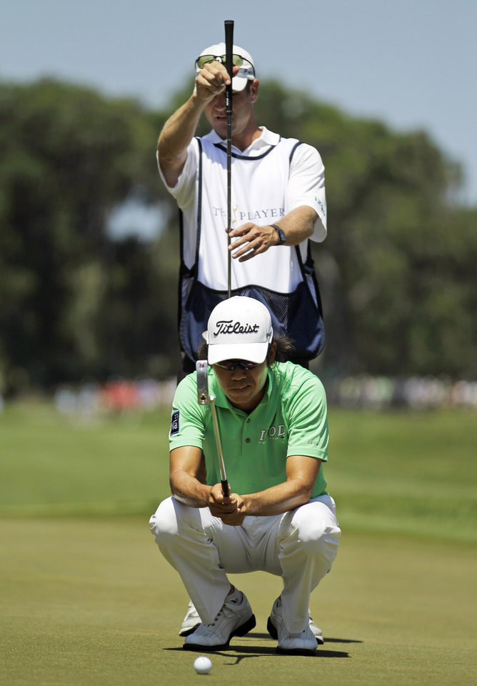 Photo -   Kevin Na and his caddie Kenny Harus, top, look over Na's line on the sixth green during the second round of the Players Championship golf tournament at TPC Sawgrass, Friday, May 11, 2012, in Ponte Vedra Beach, Fla. (AP Photo/David Goldman)