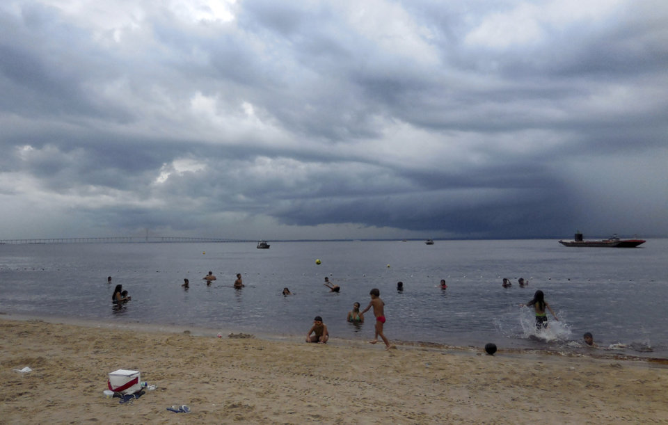 Photo - People swim in the Rio Negro in Manaus, Brasilia, Monday, June 16, 2014 despite  staying in the water despite downpours.       (AP Photo/Chris Lehourites)