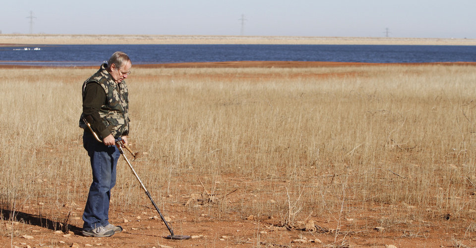 LOST METAL: Larry Nowlin, uses a metal detector as he looks for lost items at Lake Hefner in Oklahoma City, Thursday January  17, 2013. Area lakes are very low due to the recent drought. Photo By Steve Gooch, The Oklahoman