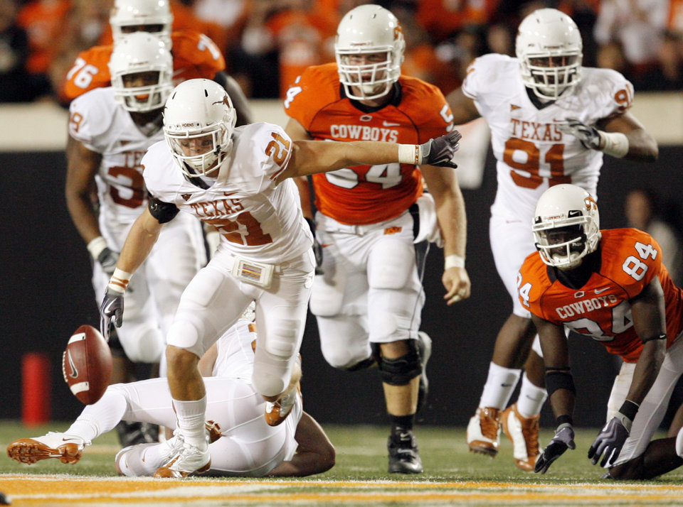 Photo - Blake Gideon (21) of Texas chases an OSU fumble in the second quarter as OSU's Andrew Lewis (54) and Hubert Anyiam (84) look on during the college football game between the Oklahoma State University Cowboys (OSU) and the University of Texas Longhorns (UT) at Boone Pickens Stadium in Stillwater, Okla., Saturday, Oct. 31, 2009. Texas recovered the fumble. Photo by Nate Billings, The Oklahoman