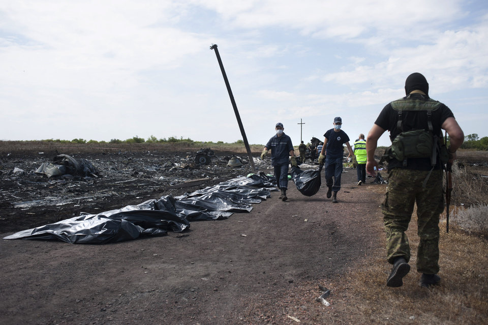 Photo - Ukrainian emergency workers carry a victim's body in a bag as a pro-Russian fighter, right back to a camera, guards the crash site of Malaysia Airlines Flight 17· near the village of Hrabove, eastern Ukraine, Sunday, July 20, 2014. Rebels in eastern Ukraine took control Sunday of the bodies recovered from downed Malaysia Airlines Flight 17, and the U.S. and European leaders demanded that Russian President Vladimir Putin make sure rebels give international investigators full access to the crash site.(AP Photo/Evgeniy Maloletka)
