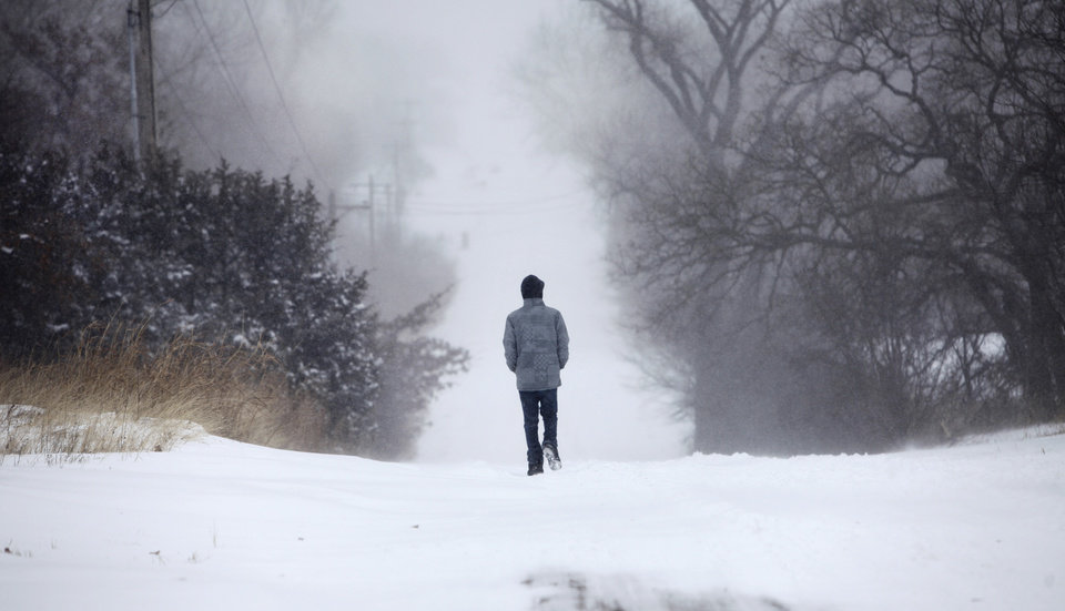 Photo - A man walks through deep snow on E. Charter Oak Rd. in Logan County, Oklahoma February  1, 2011. Photo by Steve Gooch, The Oklahoman