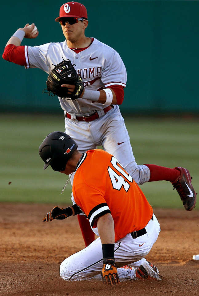 Photo - OU's Hector Lorenzana throws over OSU's Craig McConaughy at second to complete the double play in the second inning of a Bedlam baseball game between Oklahoma State University and the University of Oklahoma in Stillwater, Tuesday, April 15, 2014. Photo by Bryan Terry, The Oklahoman