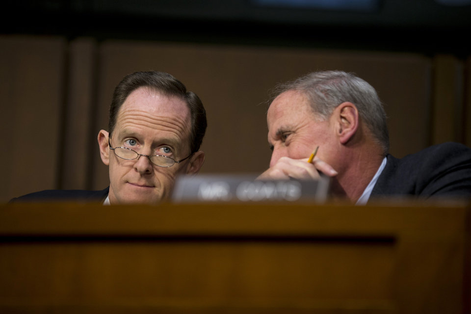Photo - Joint Economic Committee members Sen. Pat Toomey, R-Pa., left, and Sen. Dan Coats, R-Ind. talk on Capitol Hill in Washington, Thursday, Dec. 6, 2012, during the committee's hearing entitled:
