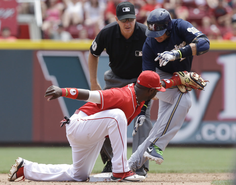 Photo - Cincinnati Reds second baseman Brandon Phillips, left, tags out Milwaukee Brewers' Aramis Ramirez at second base trying to stretch a single to a double in the fifth inning of a baseball game, Sunday, July 6, 2014, in Cincinnati. Umpire Paul Emmel watches. (AP Photo/Al Behrman)