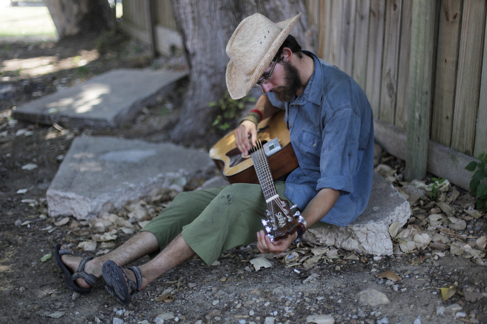 Photo - Peter Dieold, of Illinois, tunes his guitar during the Woody Guthrie Folk Festival in Okemah, Okla., Thursday, July 12, 2012.  Photo by Garett Fisbeck, The Oklahoman