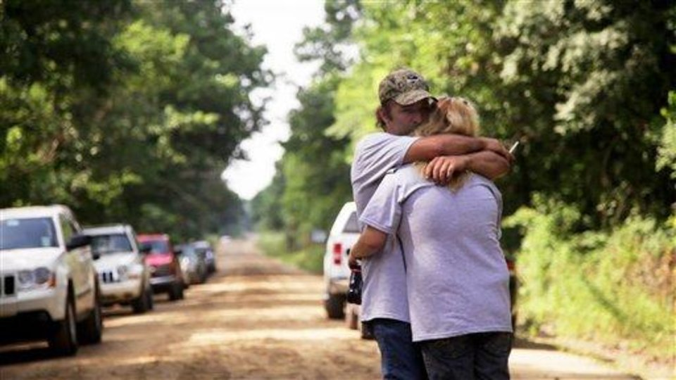 Photo - Peter and Vicki Placker comfort each other following a news conference held at the site where their daughter, Taylor Paschal-Placker, 13, and her friend, Skyla Jade Whitaker, 11, were killed on a road just north of Weleetka, Okla., Tuesday, June 8, 2010. The girls were found shot to death on June 8, 2008, along a dirt road near Weleetka. (AP Photo/Tulsa World, Adam Wisneski)