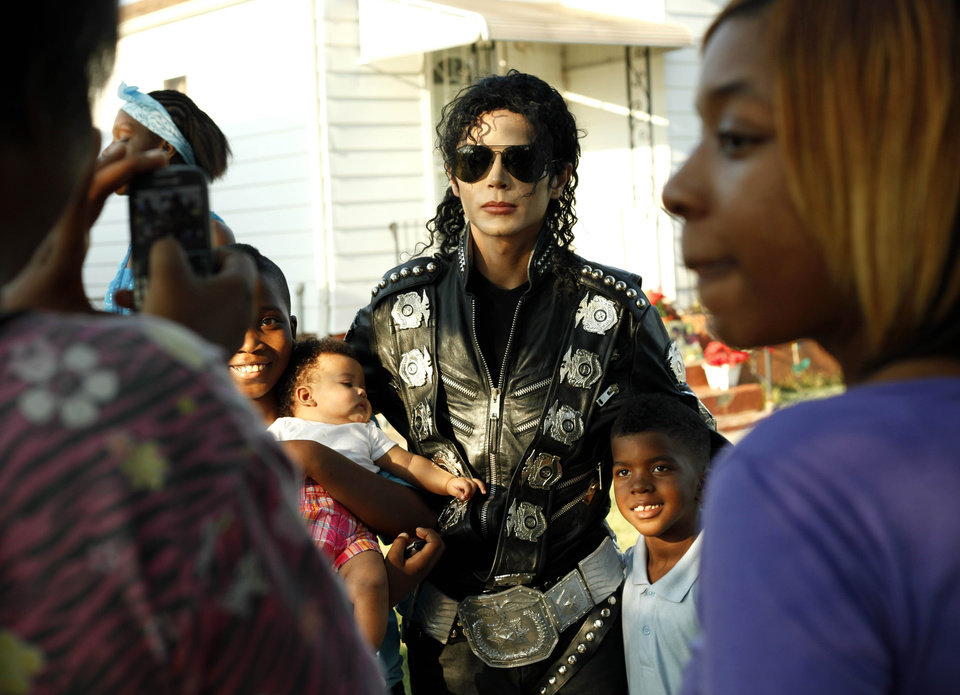 Photo -   Michael Jackson impersonator Carlo Riley from Denver, poses with three children near Jackson's boyhood home during celebrations marking what would have been Jackson's 54th birthday Wednesday, Aug. 29, 2012, in Gary, Ind. (AP Photo/Sitthixay Ditthavong)