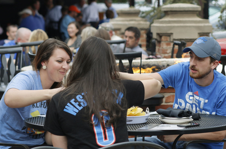 Photo -  Cristen and Chad DeJager and Alisha Jannelli, back, have dinner April 21 at Deep Deuce Grill before Game 2 of the Thunder's playoff series with Memphis. Photo by Doug Hoke, The Oklahoman   DOUG HOKE -