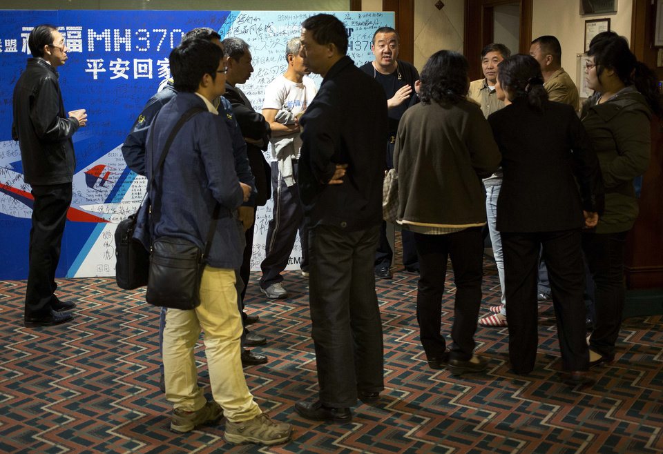 Photo - Relatives of Chinese passengers aboard the missing Malaysia Airlines flight MH370 chat outside the conference room during a briefing held by Malaysia officials at a hotel in Beijing, China Friday, April 11, 2014. Authorities are confident that signals detected deep in the Indian Ocean are from the missing Malaysian jet's black boxes, Australia's Prime Minister  Tony Abbott said Friday, raising hopes they are near solving one of aviation's most perplexing mysteries. (AP Photo/Andy Wong)