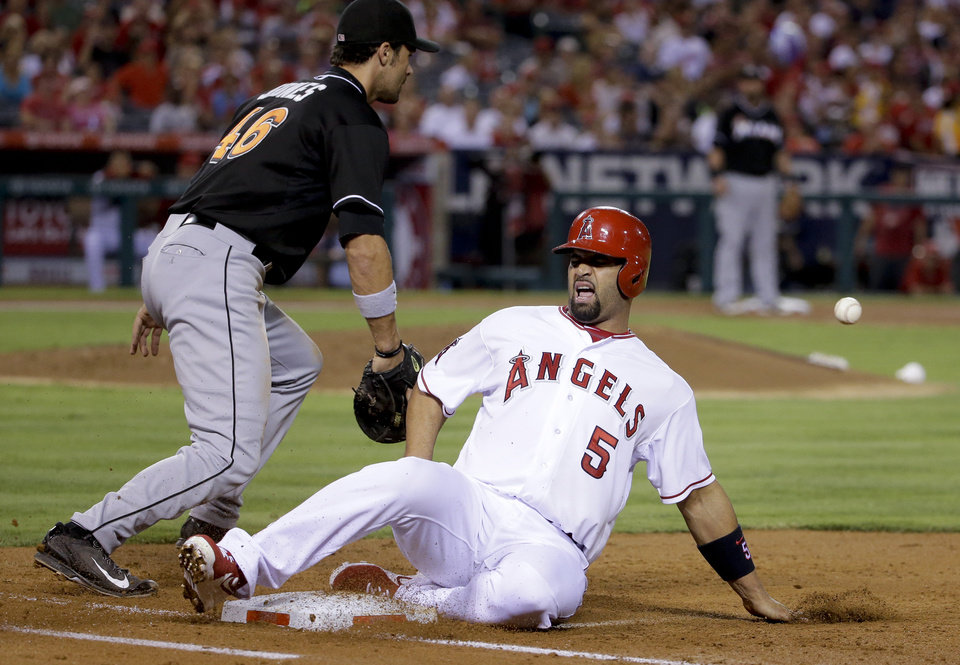 Photo - Los Angeles Angels' Albert Pujols, right, reacts after getting ht by a throw after sliding back to first as Miami Marlins first baseman Garrett Jones goes to the ball during the third inning of a baseball game in Anaheim, Calif., Tuesday, Aug. 26, 2014. (AP Photo/Chris Carlson)