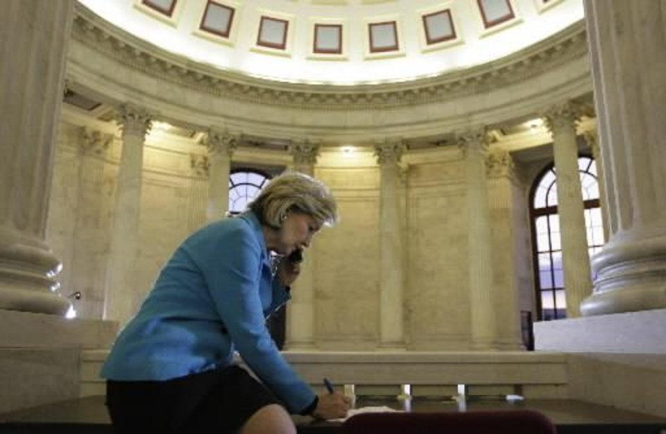 Photo - Sen. Kay Bailey Hutchison, R-Texas, takes notes as she talks on the phone about the shooting at  Fort  Hood, Texas, on Capitol Hill in Washington Thursday, Nov. 5, 2009.(AP Photo/Alex Brandon)