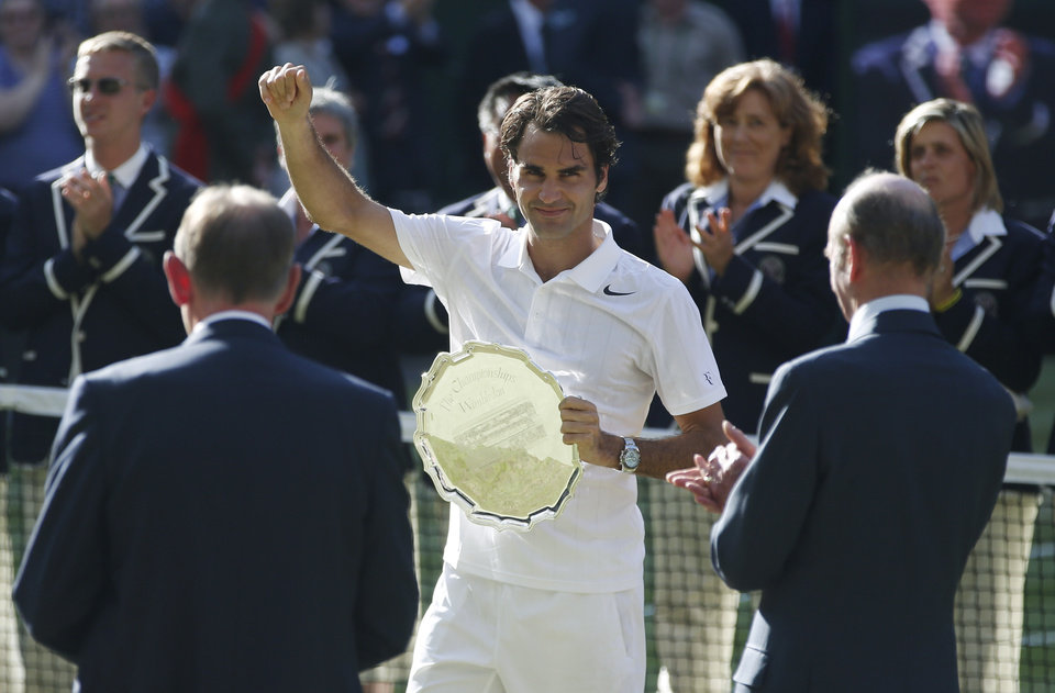 Photo - Roger Federer of Switzerland holds the runner up trophy after being defeated by Serbia's Novak Djokovic in the men's singles final at the All England Lawn Tennis Championships in Wimbledon, London, Sunday July 6, 2014. (AP Photo/Pavel Golovkin)