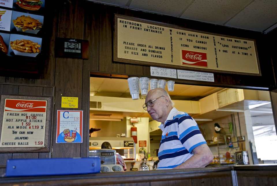 Photo - Ballard's Drive-In owner Johnny Ballard works the counter on Monday. Ballard, who turns 91 in two weeks, closes his drive-in after 61 years in business.  CHRIS LANDSBERGER - THE OKLAHOMAN