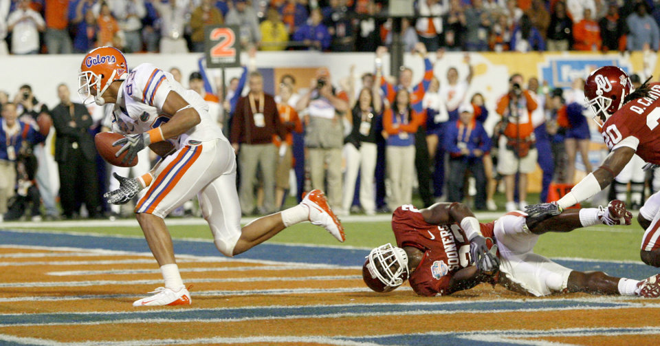 Photo - Florida's David Nelson scores a touchdown in front of OU's Keenan Clayton, center, and Quinton Carter during the second half of the BCS National Championship college football game between the University of Oklahoma Sooners (OU) and the University of Florida Gators (UF) on Thursday, Jan. 8, 2009, at Dolphin Stadium in Miami Gardens, Fla. 