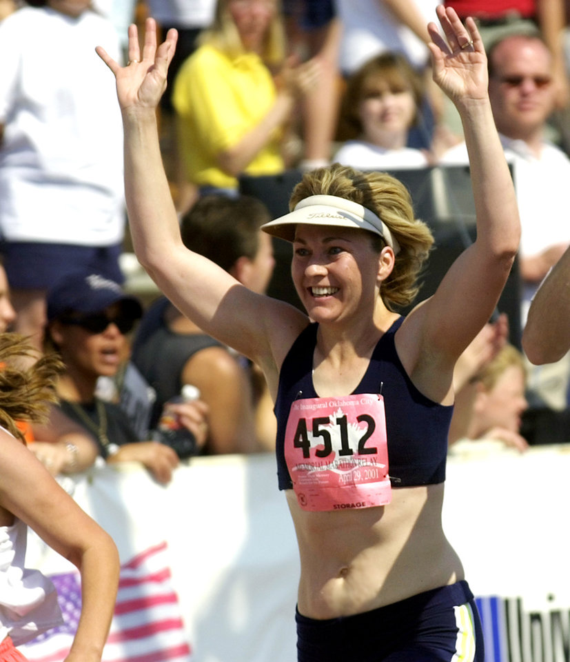 Photo - Julie Hagen of Stillwater celebrates as she finishes the Oklahoma City Memorial marathon on Sunday.  Staff photo by Bryan Terry