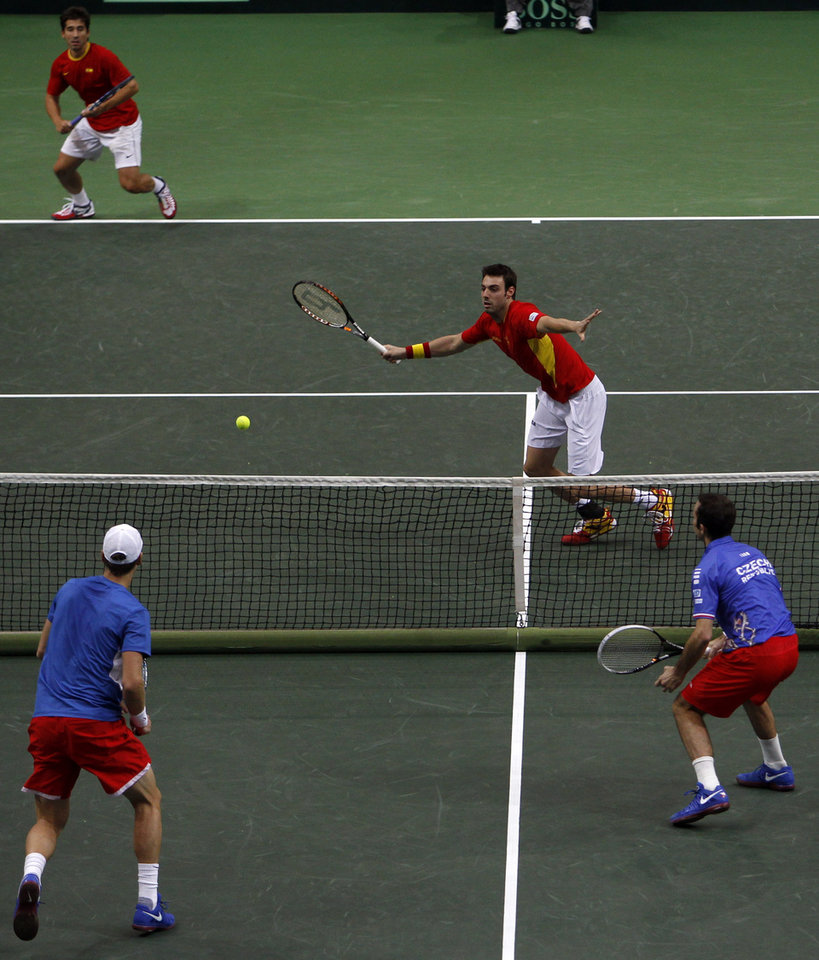 Photo -   Spain's Marcel Granollers, center, returns a ball while his doubles partner Marc Lopez, back, follows the play during their Davis Cup finals doubles tennis match against Czech Republic's Radek Stepanek, right, and Tomas Berdych, front, in Prague, Czech Republic, Saturday, Nov. 17, 2012. (AP Photo/ Marko Drobnjakovic)