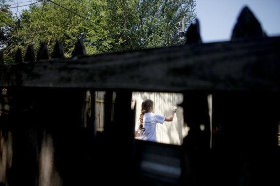 Dana Murray, 15, from the Catholic HEART Workcamp, paints a shed in the backyard of Dale Osborne in the Riverpark neighborhood in southwest Oklahoma City. <strong>ZACH GRAY - THE OKLAHOMAN</strong>