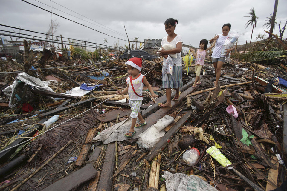 Photo - Survivors walk in typhoon ravaged Tacloban city, Leyte province, central Philippines on Tuesday, Nov. 12, 2013. The Philippines emerged as a rising economic star in Asia but the trail of death and destruction left by Typhoon Haiyan has highlighted a key weakness: fragile infrastructure resulting from decades of neglect and corruption. (AP Photo/Aaron Favila)
