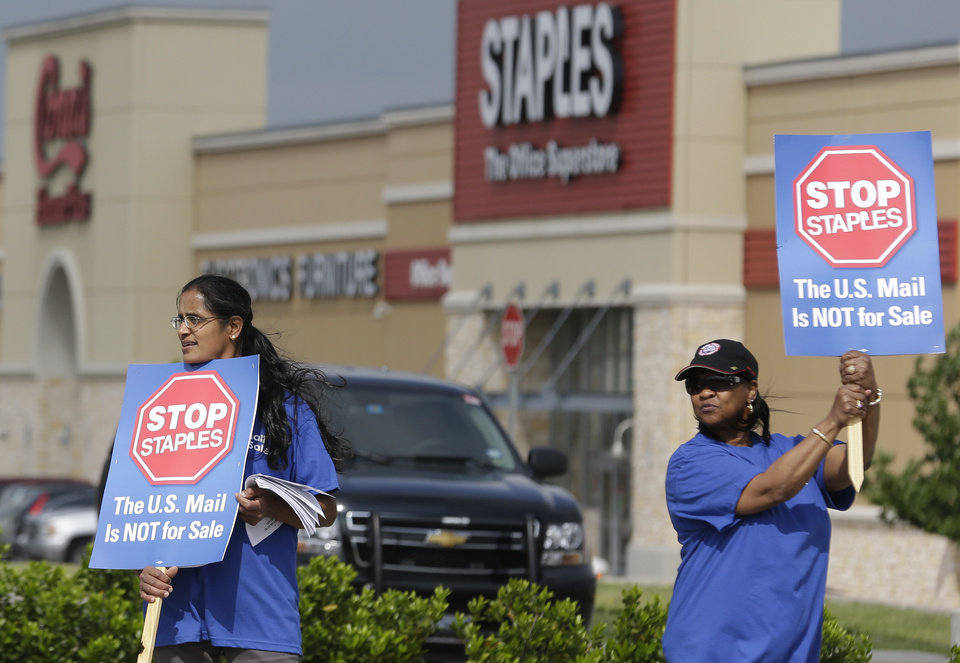 Photo - Postal worker Sophia Joseph, left, and retired postal worker Barbara Burkhalter hold signs outside a Staples store during a protest in Dallas, Thursday, April 24, 2014.  Thousands of postal workers around the nation are expected to picket outside Staples' stores to protest a pilot program of postal counters in the stores that are staffed with Staples employees. (AP Photo/LM Otero)