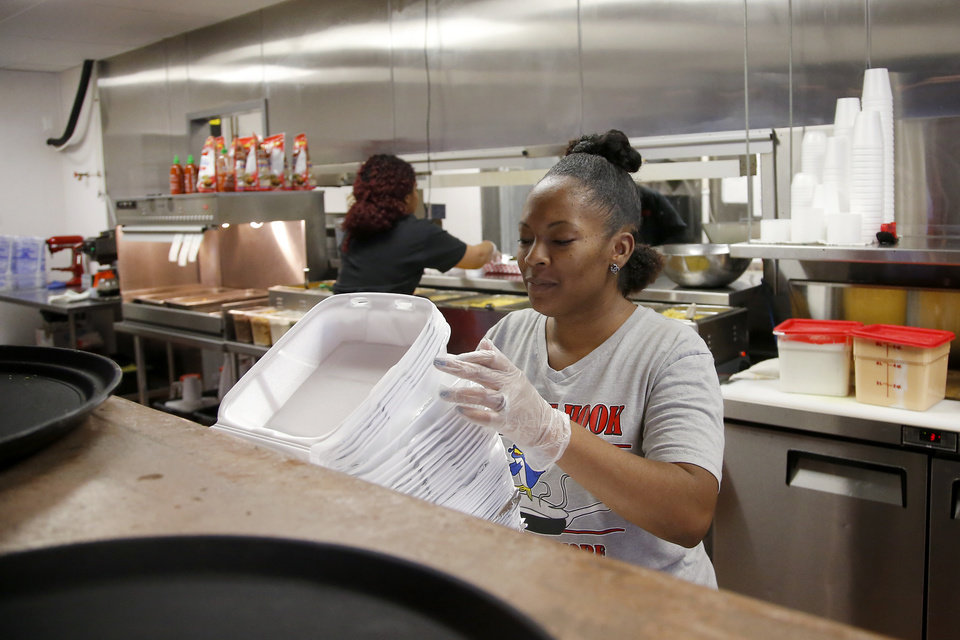 Photo -  Loniesha Tempson-Harris organizes containers at Off the Hook's south Oklahoma City location. [Photo by Bryan Terry, The Oklahoman]