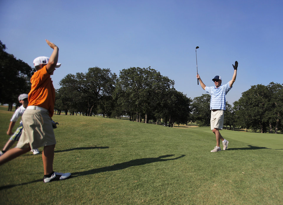 John Edmunson, of Luther, celebrates with his sons Jack, 13, and Will, 9, after chipping a ball into the cup during Family Fun Night at Kickingbird Golf Course, Saturday, June 21, 2012.  Photo by Garett Fisbeck, The Oklahoman
