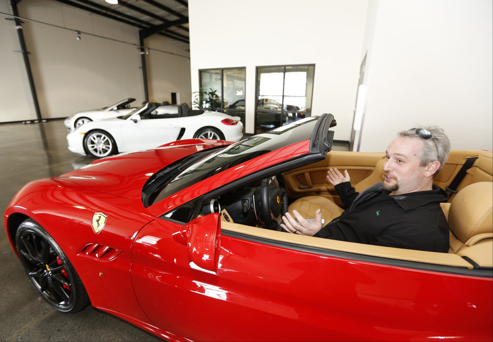 Photo - In this Wednesday, March, 26, 2014 photo,  Steve Briscoe, vice president, Industrial Air Centers, Inc., reacts as he starts the motor of a 2014 Ferrari California displayed for rent at the Enterprise Exotic Car Collection showroom near Los Angeles International Airport. (AP Photo/Damian Dovarganes)