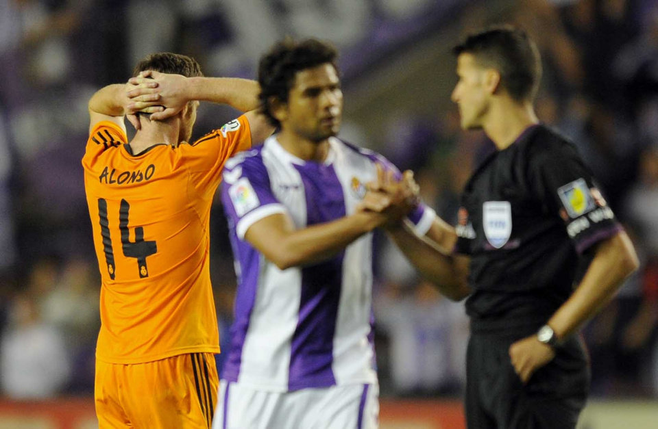 Photo - Real Madrid's midfielder Xabi Alonso, left gestures, as Real Valladolid's Colombian forward Humberto Osorioduring talks to the referee, during a Spanish La Liga soccer match at the Jose Zorrilla stadium in Valladolid, Spain, Wednesday, May 7, 2014. (AP Photo/Israel L. Murillo)