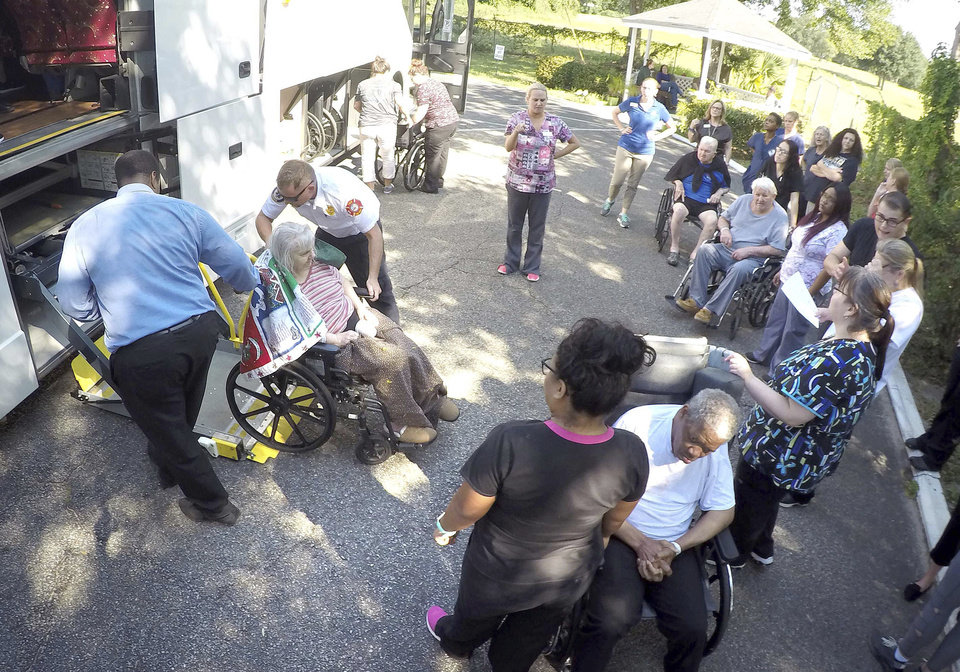Photo - Staff members at Westwood Nursing and Rehabilitation Center in Fort Walton Beach, Fla., and firefighters from Fort Walton Beach Fire Department load Hurricane Irma evacuees, who had stayed at Westwood since last Saturday, onto a bus on Wednesday Sept. 13, 2017 to head back to the their facility in Mayo, Fla. (Nick Tomecek/Northwest Florida Daily News via AP)