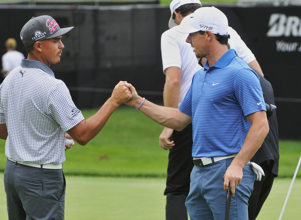 Photo - Rickie Fowler, left, shakes hands with Rory McIlroy of Northern Ireland, on the 18th green during practice at the World Golf Championships Bridgestone Invitational, Tuesday, July 29, 2014, in Akron, Ohio. (AP Photo/Phil Long)