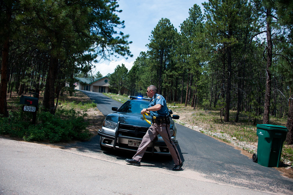 Photo - A Colorado State Patrol officer races to leave a mark on a mailbox to note that the residents of the house have been notified of the mandatory evacuation because of the Black Forest fire and have left the area, Thursday, June 13, 2013, north of Colorado Springs, Colo. A voracious wildfire driven in all directions by shifting winds destroyed at least 360 homes — a number that was likely to climb as the most destructive blaze in Colorado history burned out of control for a third day through miles of tinder-dry woods. (AP Photo/The Colorado Springs Gazette, Michael Ciaglo)  MAGS OUT
