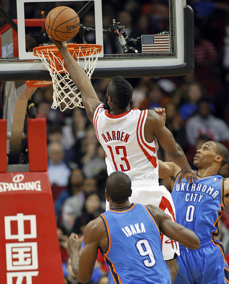 Houston Rockets guard James Harden (13) drives to the basket between Oklahoma City Thunder guard Russell Westbrook (0) and forward Serge Ibaka (9) during the first half of an NBA basketball game, Saturday, Dec. 29, 2012, in Houston. (AP Photo/Bob Levey)