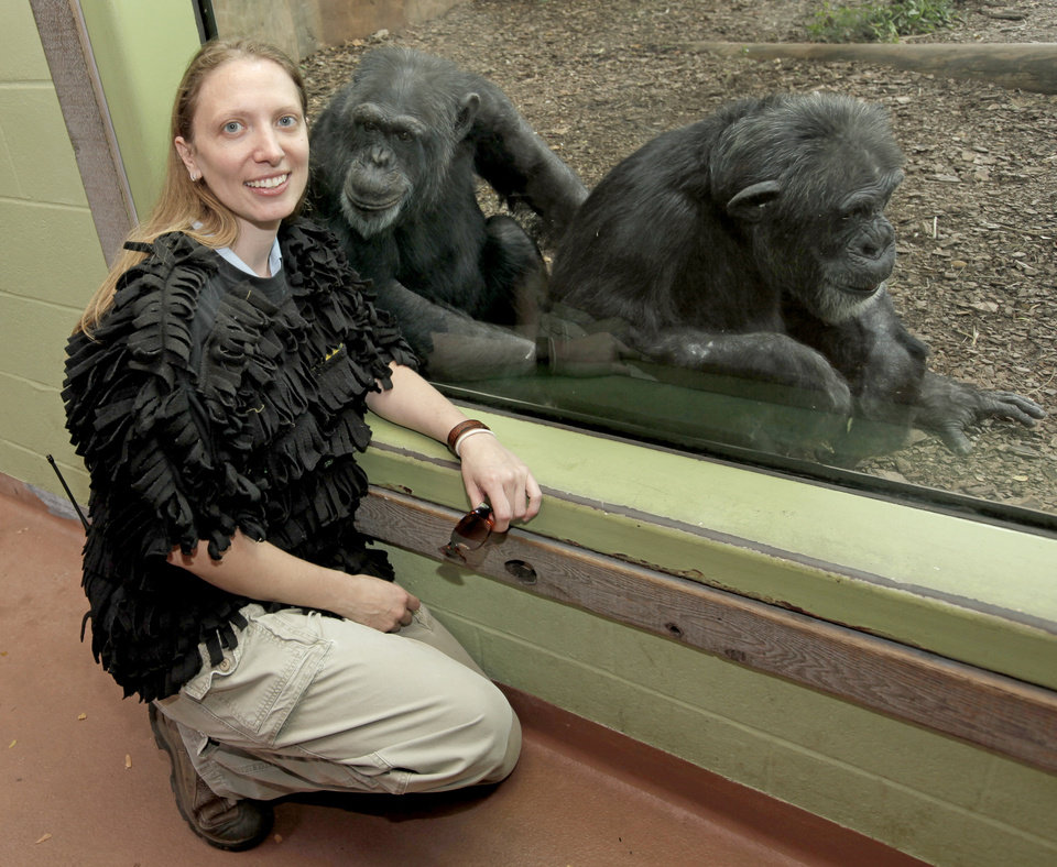 Photo - Jennifer Davis, supervisor of great apes, poses for a photo while wearing a vest made from a t-shirt and pieces of fleece that was used to teach a new orphan baby chimpanzee at the zoo to cling, at the Oklahoma City Zoo in Oklahoma City, Thursday, September 3, 2009. In the picture are two of the zoo's older chimpanzees, Jackson, left, and Qadeer. By Nate Billings, The Oklahoman ORG XMIT: KOD
