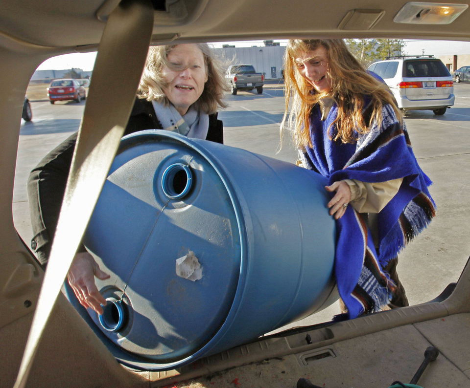 Photo - Catherine Webb, left, and Karen Chapman load a rain barrel into a car Saturday after a giveaway and workshop on how to use them in Norman. Photos by Steve Sisney, The Oklahoman